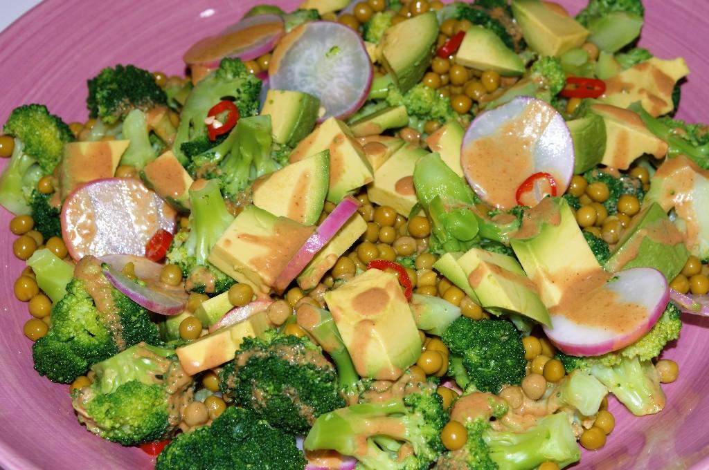 Ensalada de brócoli, aguacates y guisantes con aliño de cacahuetes.