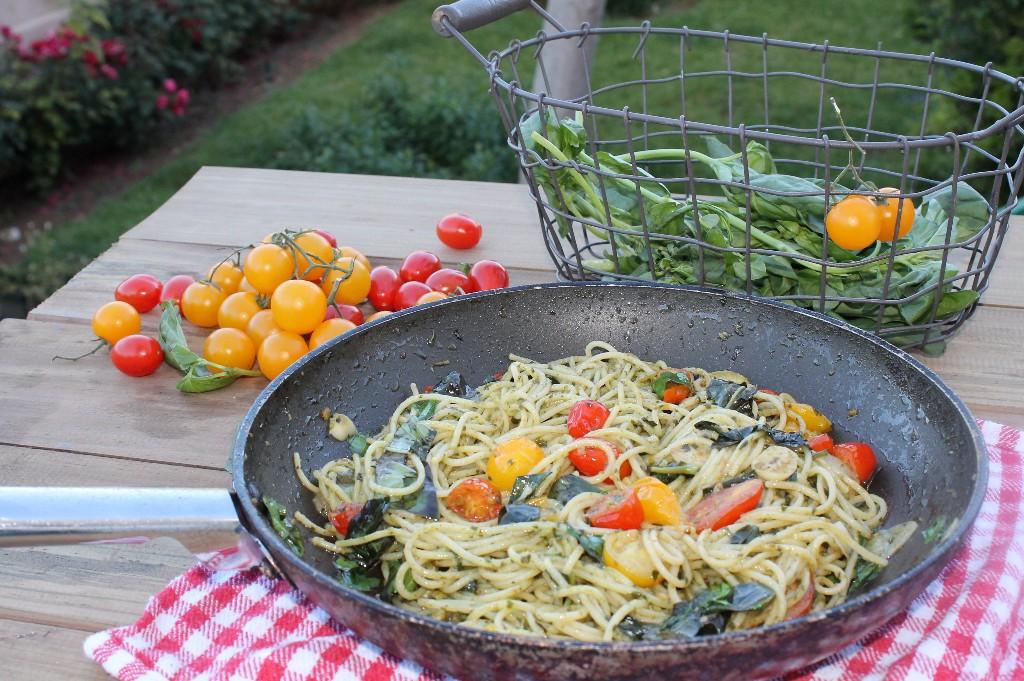 Espaguetis con pesto de albahaca y tomatitos de colores.